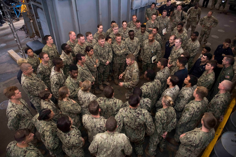 Sailors meet with an Army general in the well deck of an amphibious ship