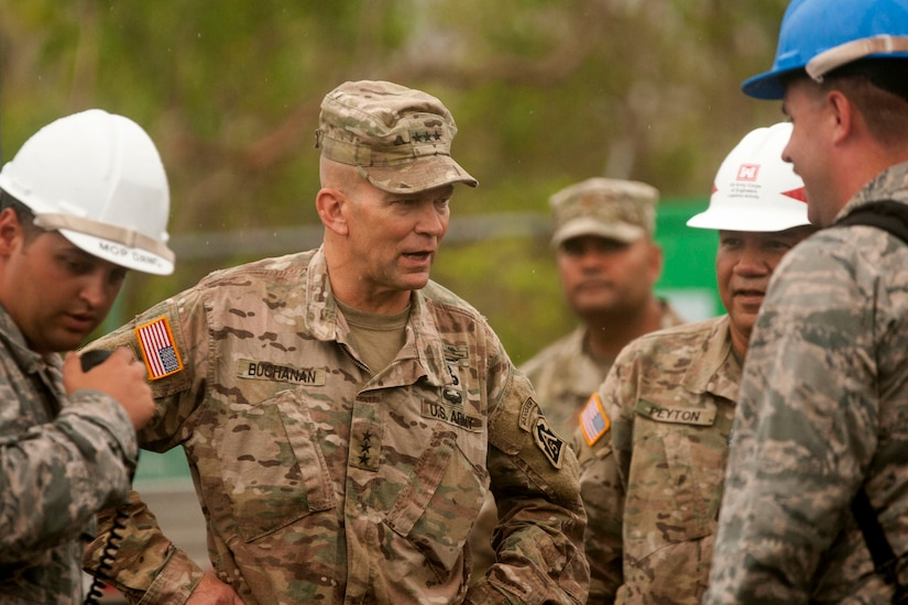 An Army general speaks with Air Force engineers