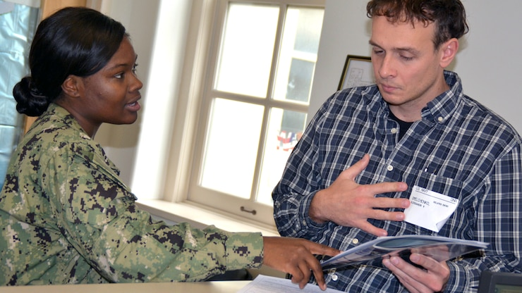 A sailor talks to a person holding papers.