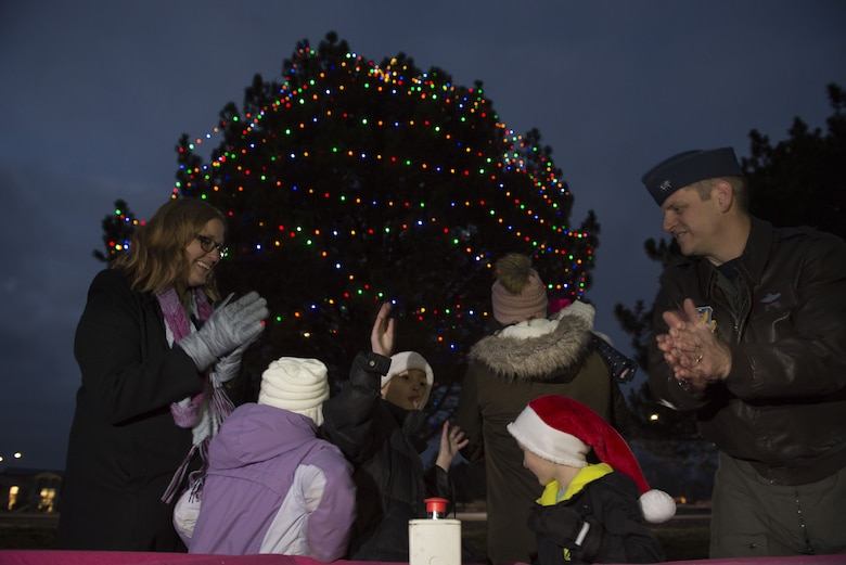Katie Powers, spouse of 366th Operations Group first sergeant, her children and Col. Joe Kunkel, 366th Fighter Wing commander, cheer as the button to light the bases Christmas tree has been pushed Dec. 8, 2017, at Mountain Home Air Force Base, Idaho. The night events consisted of the holiday parade, the base tree lighting, Christmas caroling and Gunfighter Glow. (U.S. Air Force photo by Senior Airman Lauren-Taylor Levin)