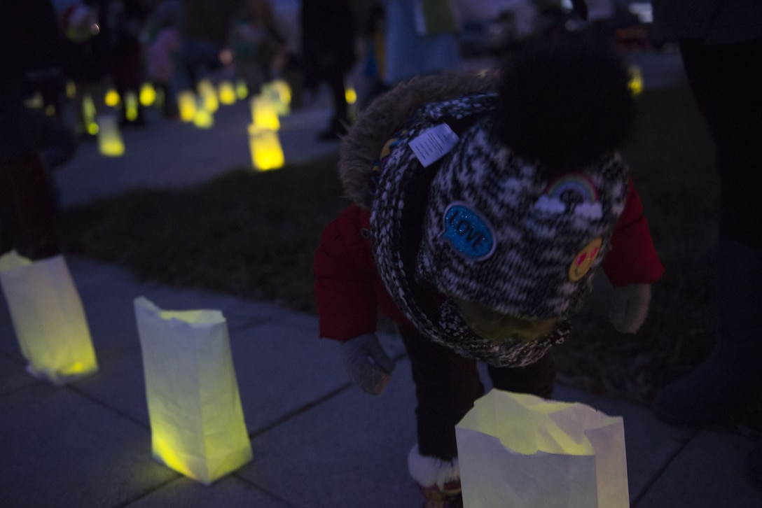 A child looks into a glowing bag during Gunfighter Glow Dec. 8, 2017, at Mountain Home Air Force Base, Idaho. Each glow stick represents an Airman who currently deployed from the 366th Fighter Wing. (U.S. Air Force photo by Senior Airman Lauren-Taylor Levin)