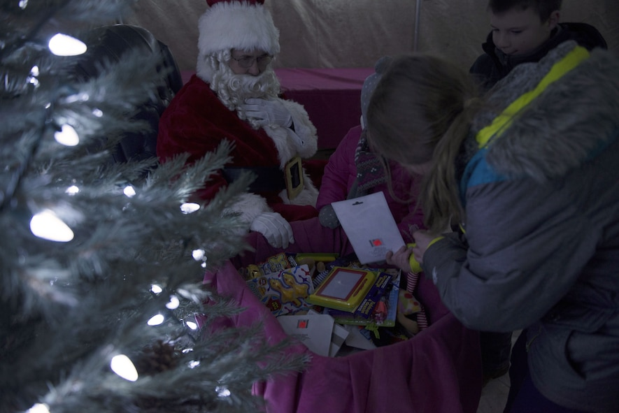 Children look through Santa's toy sack for a toy to keep Dec. 8, 2017, at Mountain Home Air Force Base, Idaho. After Gunfighter Glow families and children were able to talk to Santa and tell them what they wanted for Christmas. (U.S. Air Force photo by Senior Airman Lauren-Taylor Levin)