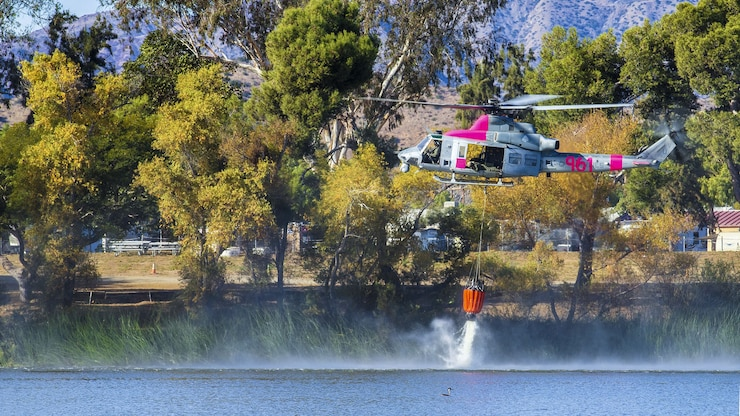 A helicopter fills an orange bucket with water from a lake.