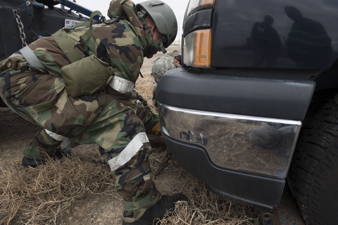 Photograph of Senior Airman Jeffrey Robison, 366th Logistics Readiness Squadron vehicle operator, places a chain on a simulated damaged vehicle Dec. 6, 2017, at Mountain Home Air Force Base, Idaho. Before any vehicle can be towed it must have a two part secure system or else the vehicle can not be lifted. (U.S Air Force photo by Senior Airman Lauren-Taylor Levin)