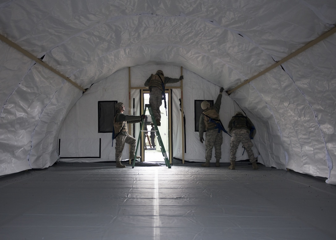 Photo of Airmen from the 366th Civil Engineer Squadron finish the interior of a tent during an exercise Dec. 7, 2017, at Mountain Home Air Force Base, Idaho. The base participated in a week-long training exercise to train for potential real world contingencies. (U.S. Air Force photo by Senior Airman Chester Mientkiewicz)