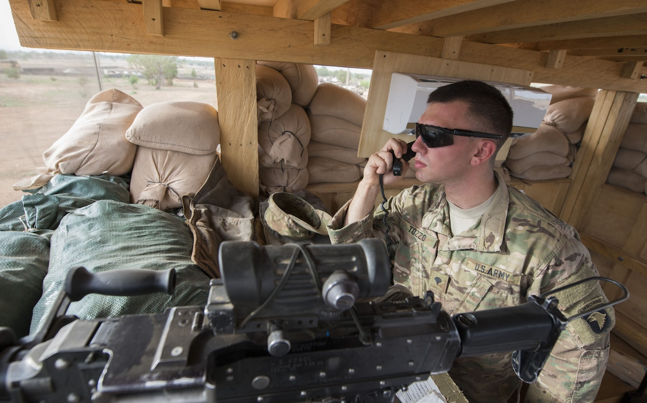 A soldier speaks into a radio microphone