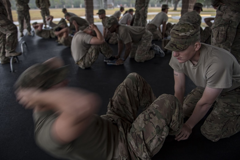 Airmen from the 820th Base Defense Group perform the sit-up portion of the Army Physical Fitness Test during an Army Air Assault readiness assessment, Dec. 7, 2017, at Camp Blanding, Fla. The AAA readiness assessment is designed to prepare Airmen for the Army Air Assault School curriculum as well as its physical and mental stressors. During AAA, U.S. troops are taught an array of skills associated with rotary-winged aircraft. These skills widen the 820th BDG's ability to swiftly deploy and defend. (U.S. Air Force photo by Senior Airman Daniel Snider)
