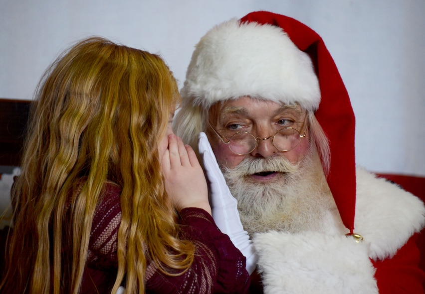 Santa listens as a girl whispers her holiday wishes to him at Dobbins Air Reserve Base, Ga. Dec. 3, 2017. Over the course of the busy December drill weekend, the Clauses set up shop in a hangar to hear the holiday wishes of military members and their families. (U.S. Air Force photo by Don Peek)