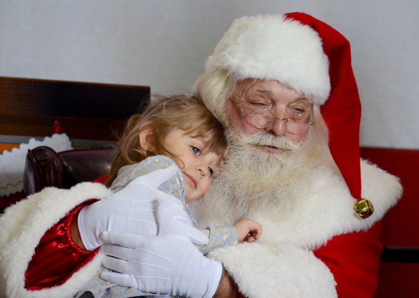 Santa hugs a child after she tells him her holiday wishes at Dobbins Air Reserve Base, Ga. Dec. 3, 2017. Sitting on a stage in a hangar usually reserved for commander's calls and aircraft maintenance, children lined up for what seemed like miles to ask the Clauses for everything from bicycles to video games. (U.S. Air Force photo by Don Peek)