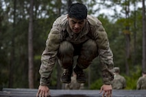 Airman Tyler Carpenter, 823d Base Defense Squadron fireteam member, leaps over a log obstacle during an Army Air Assault readiness assessment, Dec. 7, 2017, at Camp Blanding, Fla. The AAA readiness assessment is designed to prepare Airmen for the Army Air Assault School curriculum as well as its physical and mental stressors. During AAA, U.S. troops are taught an array of skills associated with rotary-winged aircraft. These skills widen the 820th Base Defense Group's ability to swiftly deploy and defend. (U.S. Air Force photo by Senior Airman Daniel Snider)