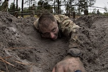 Airman 1st Class Brian Piperato, 824th Base Defense Squadron fireteam member, low crawls through an obstacle during an Army Air Assault readiness assessment, Dec. 7, 2017, at Camp Blanding, Fla. The AAA readiness assessment is designed to prepare Airmen for the Army Air Assault School curriculum as well as its physical and mental stressors. During AAA, U.S. troops are taught an array of skills associated with rotary-winged aircraft. These skills widen the 820th Base Defense Group's ability to swiftly deploy and defend. (U.S. Air Force photo by Senior Airman Daniel Snider)
