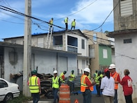 U.S. Army Corps of Engineers employees who are deployed to Puerto Rico as part of the Corps' Temporary Roofing team which oversees the installation of blue plastic sheeting on to damaged roofs until arrangements for permanent repairs are made.