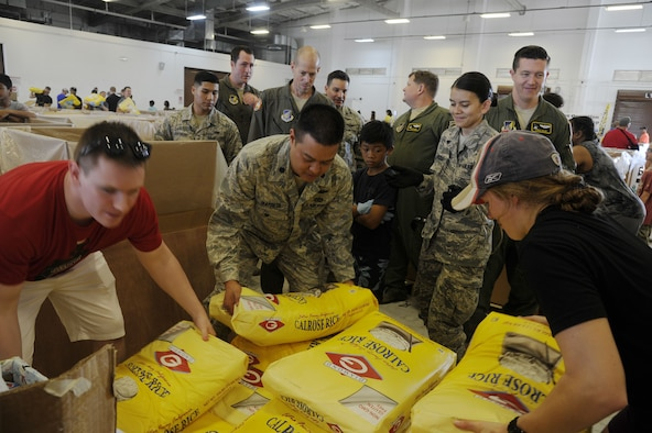 U.S. Air Force Lt. Col. Melvin Ibaretta, the deputy commander of the Air Force Reserve's 624th Regional Support Group, works with members of the 44th Aerial Port Squadron by grabbing a bag of rice to include in a Christmas bundle during Operation Christmas Drop Dec. 9, 2017, at Andersen Air Force Base, Guam. Operation Christmas Drop has been providing critical supplies to 56 Micronesian Islands since 1952. The 44th Aerial Port Squadron supports the 624th Regional Support Group's mission of providing combat readiness, quality management and peacetime deployments in the Pacific area of responsibility. (U.S. Air Force photo by Master Sgt. Theanne Herrmann)