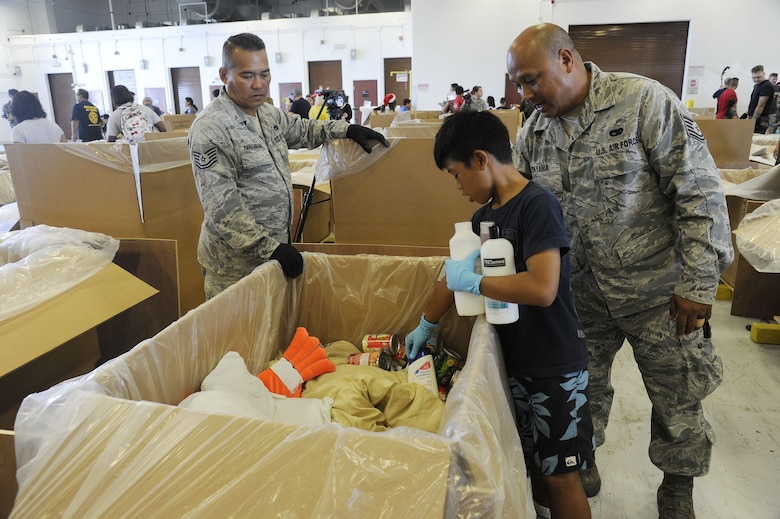 Reserve Citizen Airmen Tech. Sgt. Amon Tayama, of Baza Gardens, Guam, and Tech. Sgt. James Pangindian, of Dededo, Guam, both members of the Air Force Reserve's 44th Aerial Port Squadron, along with Tayam's nephew fill a bundle full of critical supplies during Operation Christmas Drop Dec. 9, 2017, at Andersen Air Force Base, Guam. Operation Christmas Drop has been providing critical supplies to 56 Micronesian Islands since 1952. The 44th Aerial Port Squadron supports the 624th Regional Support Group's mission of providing combat readiness, quality management and peacetime deployments in the Pacific area of responsibility. (U.S. Air Force photo by Staff Sgt. Daena Mansapit)