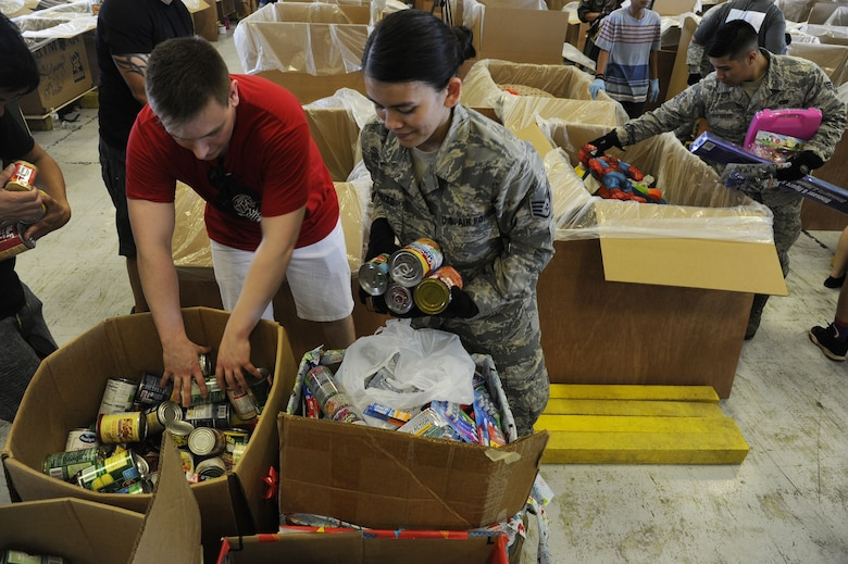 Reserve Citizen Airmen Staff Sgt. Kaija Garrido, of Sinajana, Guam, and Senior Airman Aleron Guerrero, of Mangilao, Guam, air transportation specialists from the 44th Aerial Port Squadron help fill boxes full of critical supplies during Operation Christmas Drop Dec. 9, 2017, at Andersen Air Force Base, Guam. Operation Christmas Drop has been providing critical supplies to 56 Micronesian Islands since 1952. The 44th Aerial Port Squadron supports the 624th Regional Support Group's mission of providing mission essential combat readiness, quality management and peacetime deployments in the Pacific area of responsibility. (U.S. Air Force photo by Staff Sgt. Daena Mansapit)