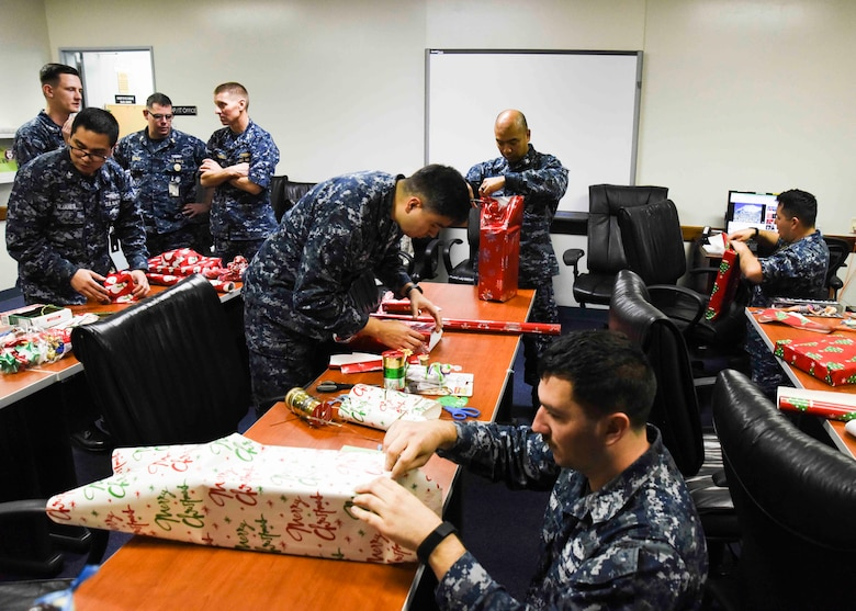 Sailors, assigned to Commander Submarine Group 7, wrap gifts intended for less fortunate children in Yokohama, Japan. The Submarine Group 7 First Class Petty Officer Association participated in a holiday gift drive for 64 underprivileged children in the Yokohama area.