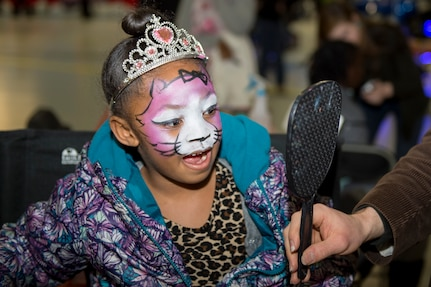 Jailynn Mercer, Parents and Children Fighting Cancer holiday party attendee, looks at her reflection after having her face painted on Joint Base Andrews, Md., Dec. 9, 2017. Face painting, a puppet show and dance performances were some of the many activities children were able to enjoy.