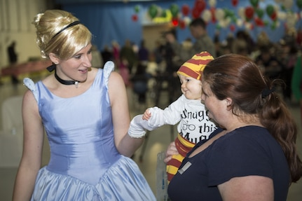 Cinderella greets Tiffany and Samuel Barnett, Parents and Children Fighting Cancer holiday party attendees, during the event's 30th anniversary on Joint Base Andrews, Md., Dec. 9, 2017. Volunteers dressed up as popular characters and interacted with visitors. Hangar 3 was turned into a winter wonderland to allow military families whose lives have been affected by cancer to gather together and enjoy the free celebration.
