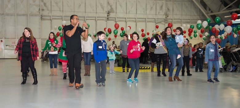 30th Annual Parents and Children Fighting Cancer holiday party attendees dance during the festive celebration in Hangar 3 on Joint Base Andrews, Md., Dec. 9, 2017. During performance breaks, guests were able to dance to various songs throughout the event.