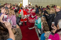 Mr. and Mrs. Santa Claus greet Parents and Children Fighting Cancer holiday party attendees in Hangar 3 on Joint Base Andrews, Md., Dec. 9, 2017. The special guests also visited children who were unable to attend the event at Walter Reed National Military Medical Center. This year marked the 30th anniversary of the JBA Fisher House event.