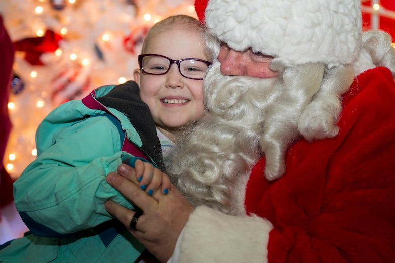 Erin Roseberry, Parents and Children Fighting Cancer holiday party attendee, smiles while sitting on Mr. Santa Claus' lap on Joint Base Andrews, Md., Dec. 9, 2017. Mr. and Mrs. Claus presented children and families with gifts during the 30th annual celebration.