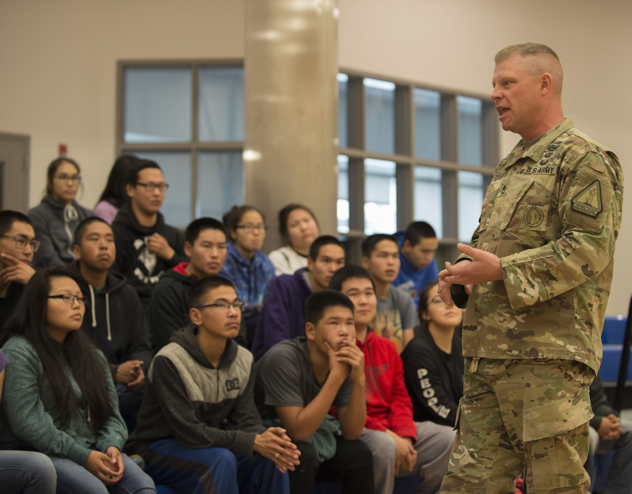 A soldier speaks to high school students during a recruiting visit