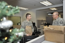 U.S. Air Force Airman 1st Class Nathan Greer, 20th Comptroller Squadron (CPTS) customer service representative, left, receives holiday cookies from Master Sgt. Raymond Lego, 20th CPTS first sergeant, at Shaw Air Force Base, S.C., Dec. 7, 2017.