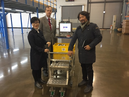 O, Hyon Yong, Dave Harris, and Kim, Yong Ki examining the Taegu Tec mobile cart. The cart is light weight, easily manuverable, has an inexpensive power supply and a built-in step ladder to work in the under mezzine walk and pick area.