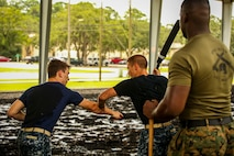 Midshipman Theo Freidenrich (left) and Midshipmen Austin Pitcher (right) practice Marine Corps Martial Arts Program techniques aboard Marine Corps Air Station Beaufort, Aug. 8. The Midshipmen visited the air station as part of their summer cruise, to experience the aviation side of the Marine Corps. While aboard MCAS Beaufort, they visited Marine Aircraft Group 31, visited F/A-18 Hornet squadrons, VMFAT-501, and took a MCMAP class.