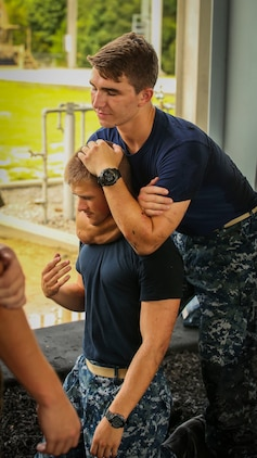 Midshipman Austin Pitcher (left) and Midshipmen Theo Freidenrich (right) are taught Marine Corps Martial Arts Program techniques aboard Marine Corps Air Station Beaufort, Aug. 8. The Midshipmen visited the air station as part of their summer cruise, to experience the aviation side of the Marine Corps. While aboard MCAS Beaufort, they visited Marine Aircraft Group 31, visited F/A-18 Hornet squadrons, VMFAT-501, and took a MCMAP class.