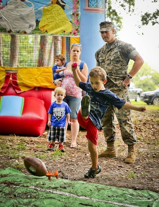 A boy kicks a football as part of a game during the 2017 Military Appreciation Day aboard Laurel Bay Housing, Aug. 26. The Beaufort Regional Chamber of Commerce hosted the event to thank service members and their families for contributions made to the Tri-command area. During the event, service members and their families could visit sponsored booths, play games, and enjoy free food.