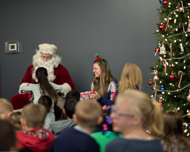 Santa passes out gifts to children at a holiday party sponsored by the Reconnaissance Crew's Booster Club in Dec. 9, 2017, in Bellevue, Nebraska. This was the 44th annual party the RCBC has put on. The event serves as a way for the service members of Offutt Air Force Base to give back to the local community. (U.S. Air Force photo by Senior Airman Jacob Skovo)