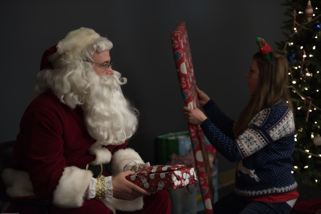 Santa and U.S. Air Force Captain Mary, 343rd Reconnaissance Squadron, passes out gifts to children at a holiday party sponsored by the Reconnaissance Crew's Booster Club in Dec. 9, 2017, in Bellevue, Nebraska. 91 children participated in the 44th annual RCBC holiday party. (U.S. Air Force photo by Senior Airman Jacob Skovo)