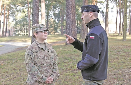 "Spc. Courtney Roth, an intelligence analyst assigned to the 82nd Brigade Engineer Battalion, 2nd Armored Brigade Combat Team, 1st Infantry Division, speaks with a Polish military officer about her Polish lineage Nov. 18. Roth is among the Dagger Brigade's ""heel-to-toe"" rotation of U.S. Soldiers ready to train with allied and partnered nations to demonstrate combat proficiencies and capabilities during the multinational exercises across Central Europe named Operation Atlantic Resolve."