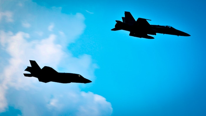 """An F-35B Lightning II Joint Strike Fighter and an F/A-18C Hornet fly over-head during the playing of the Marine Corps Hymn during a Relinquishment of Command Ceremony aboard Marine Corps Air Station Beaufort, Sept. 22. During the ceremony, Lt. Col. Michael P. Brennan relinquished command of """"The Flying Leathernecks"""" and then cased the squadron colors for transport. The squadron will stand up aboard Marine Corps Air Station Yuma, Ariz. as an F-35B Lightning II Joint Strike Fighter squadron."""