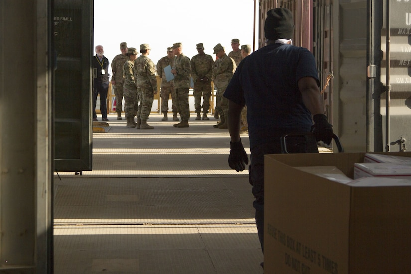 Soldiers standing outside warehouse.