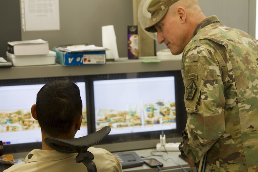 Two soldiers looking at computer screen.