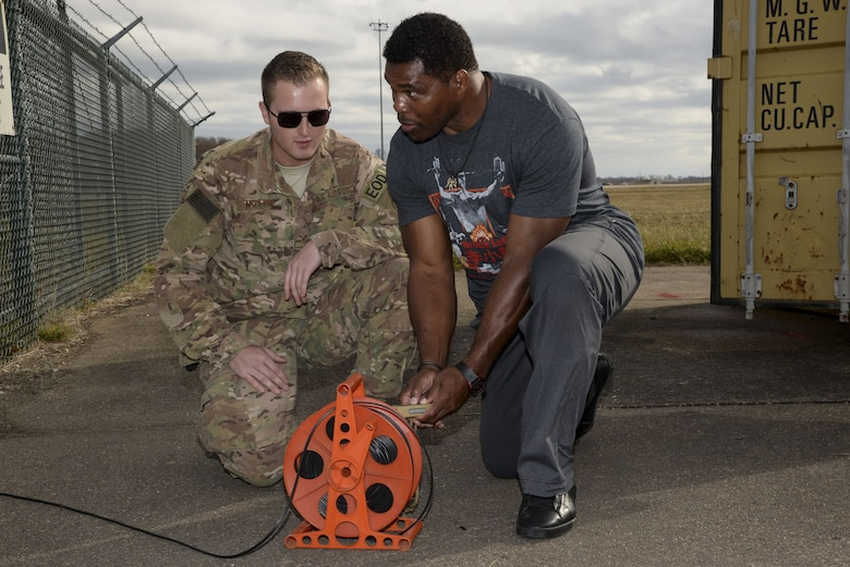 Senior Airman Joel Miller, 436th Civil Engineer Squadron explosive ordnance disposal technician, watches as Herschel Walker detonates a stick of C-4 Plastic Explosives Dec. 5, 2017, at the EOD range on Dover Air Force Base, Del. Walker visited Airmen from several units to see what they do and speak with them about the importance of mental health. (U.S. Air Force photo by Staff Sgt. Aaron J. Jenne)