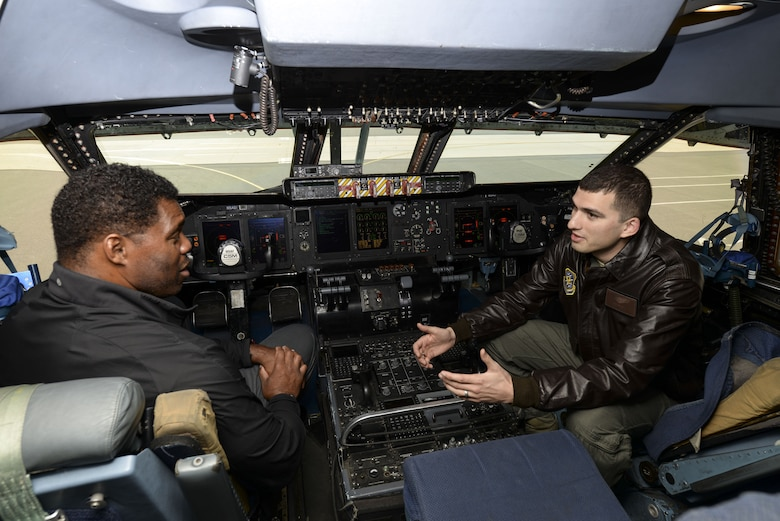 Capt. Eric Wilde II, 9th Airlift Squadron standardization evaluation liaison officer, describes the operation of a C-5M Super Galaxy to professional athlete, Herschel Walker, during a tour Dec. 6, 2017, at Dover Air Force Base, Del. Subject matter experts explained key aspects of Dover AFB operations to Walker, who shared personal stories of overcoming physical and mental hardships throughout his life. (U.S. Air Force photo by Staff Sgt. Aaron J. Jenne)