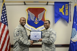 Senior Airman Ramel Hicks, right, 628th Medical Group health services manager and command support staff administrator, receives the Diamond Sharp Award certificate from Tech. Sgt. Robert Niter, left, 628th MDG interim first sergeant, in the 628th MDG conference room at Joint Base Charleston, S.C., Dec. 12, 2017.