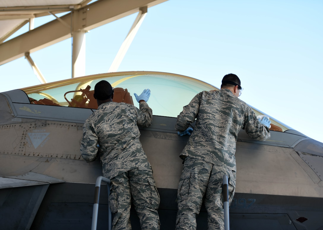 U.S. Air Force Senior Airman Gerald Austin (left), 44th Fighter Group, 44th Maintenance Squadron aircraft maintenance journeyman, and Col. Michael Hernandez, 325th Fighter Wing commander (right), clean the canopy of an F-22 Raptor at Tyndall Air Force Base, Fla., Nov. 3, 2017. Austin was selected to be shadowed by the commander for the Airman Shadow Program, a program that allows exceptional Airmen the opportunity to showcase their daily duties while interacting with the base commander. (U.S. Air Force photo by Airman 1st Class Isaiah J. Soliz/Released)