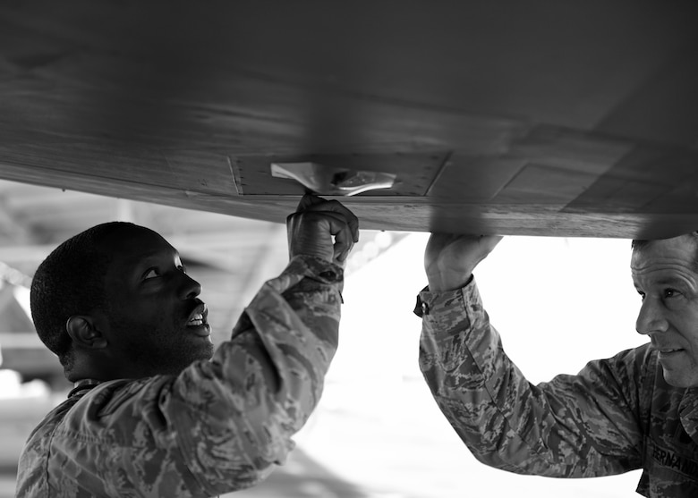 U.S. Air Force Senior Airman Gerald Austin (left), 44th Fighter Group, 44th Maintenance Squadron aircraft maintenance journeyman, describes a facet of his job duties to Col. Michael Hernandez, 325th Fighter Wing commander, while participating in the Airman Shadow Program at Tyndall Air Force Base, Fla., Nov. 3, 2017. Austin was selected by 44th FG leadership to show the wing commander the responsibilities associated with being an F-22 Raptor crew chief. (U.S. Air Force photo by Airman 1st Class Isaiah J. Soliz/Released)