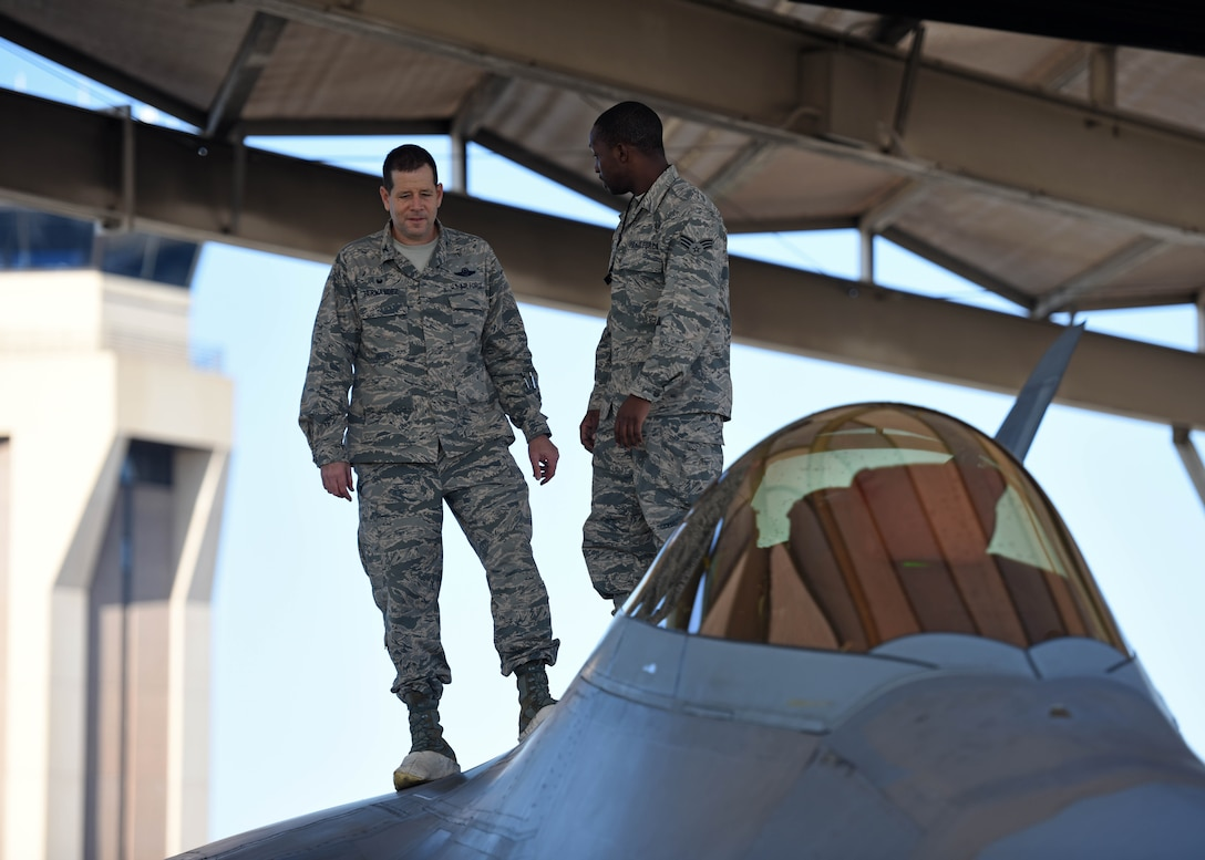 U.S. Air Force Senior Airman Gerald Austin (right), 44th Fighter Group, 44th Maintenance Squadron aircraft maintenance journeyman, stands atop an F-22 Raptor with Col. Michael Hernandez, 325th Fighter Wing commander, while participating in the Airman Shadow Program at Tyndall Air Force Base, Fla., Nov. 3, 2017. Austin was chosen by his leadership to showcase his duties as an F-22 Raptor crew chief to the commander. (U.S. Air Force photo by Airman 1st Class Isaiah J. Soliz/Released)