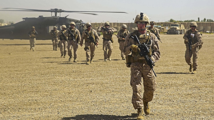Marines carry weapons as they depart a helicopter before a meeting.