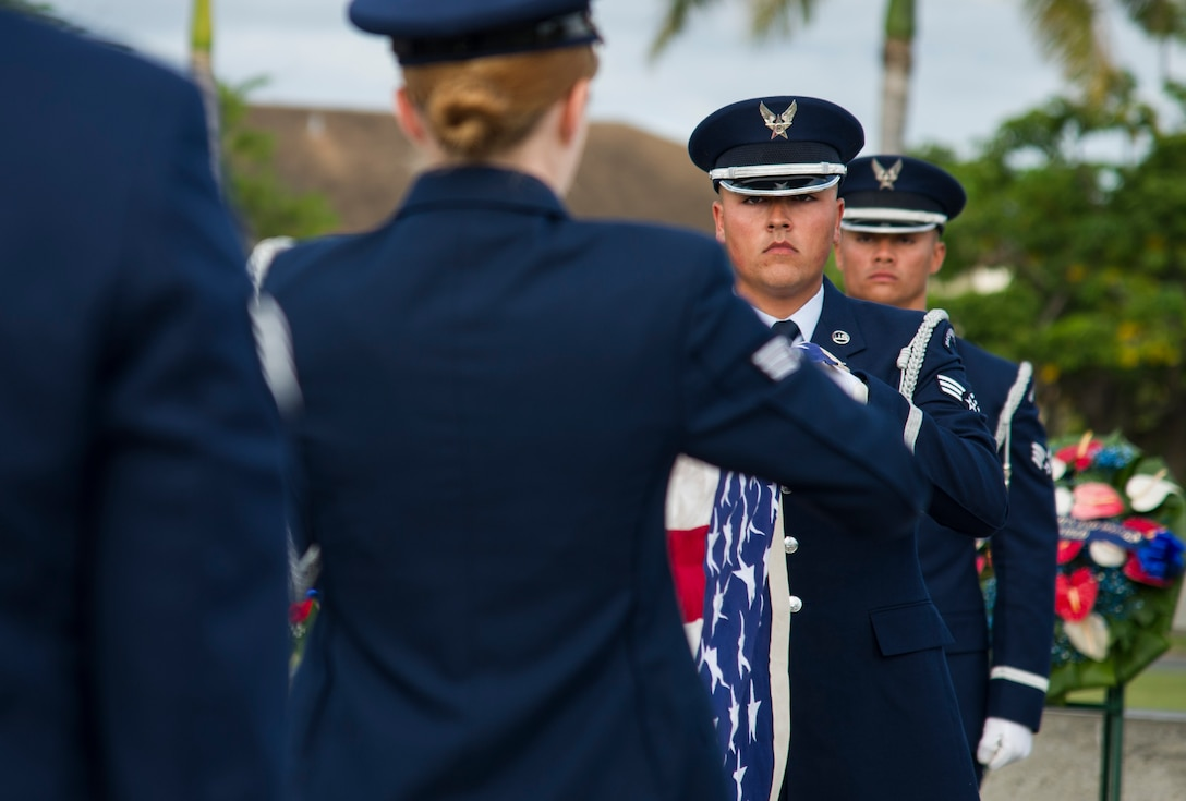 Members of the Hickam Honor Guard fold a U.S. flag.