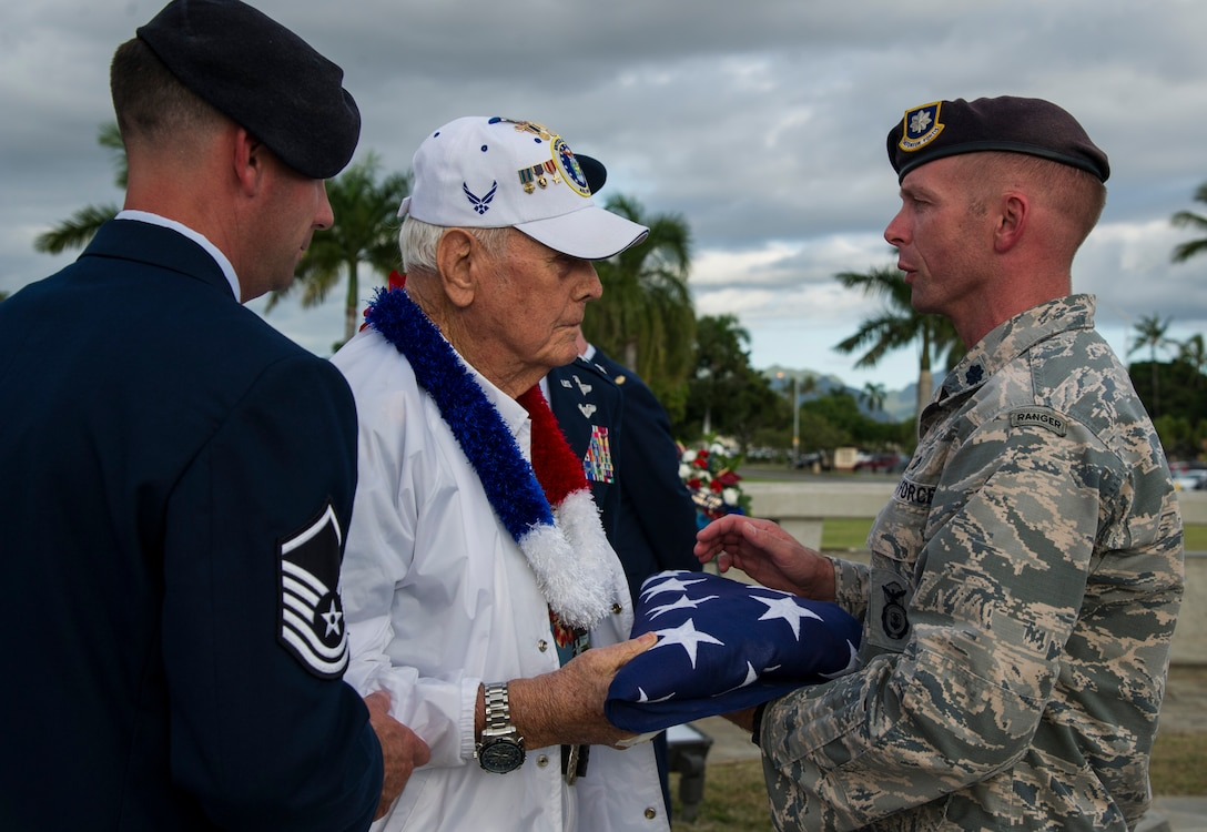 Lt. Col. Walter Sorenson, Joint Base Security commander, presents a U.S. flag to former Tech. Sgt. Durward Swanson.