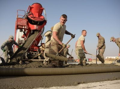 Airmen from six civil engineering job specialties, assigned to the 332nd Expeditionary Civil Engineer Squadron, work together to pour, flatten and edge a new concrete slab on a runway at an undisclosed location in Southwest Asia Nov. 28, 2017.