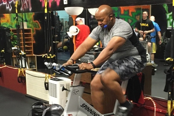 A service member works out on a stationary bike.