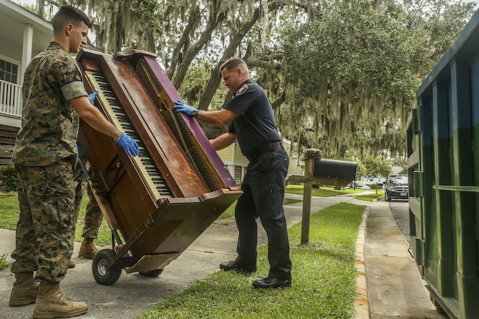 Ron Videtto, right and Lance Corporal Alfonso Quevedo, left prepare a piano on a handcart as part of  a job to help a family affected by a house fire aboard Marine Corps Recruit Depot, July 27.  The Provost Marshals Office volunteered their time to help the family in need as part of their mission to protect and serve. Videtto and Quevedo work aboard  Marine Corps Recruit Depot Parris Island.