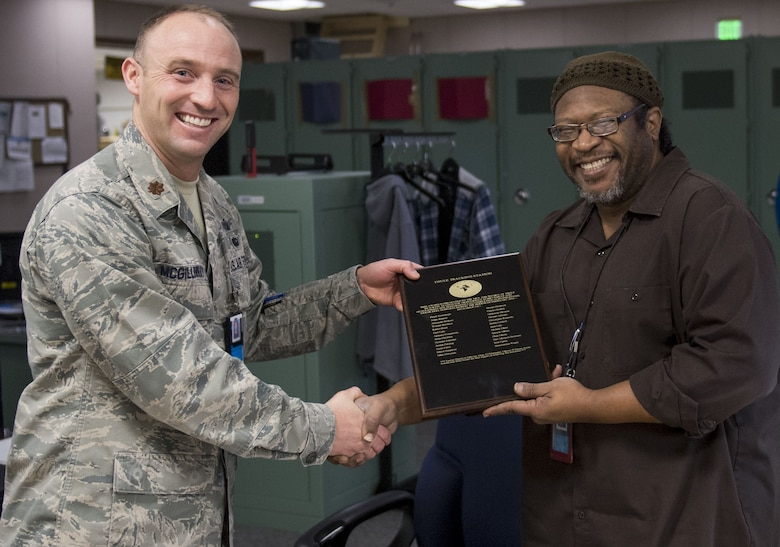 Maj. William McGillivray, 23rd Space Operations Squadron Detachment 1 commander, presents a plaque commemorating 50,000 error-free supports to George Goodrum, Det. 1 site manager, at Thule Air Base, Greenland, Dec. 11, 2017. A support involves contacting a satellite from a ground tracking station and receiving and sending data. (Badges blurred for security purposes.) (U.S. Air Force photo by Tech. Sgt. David Salanitri)